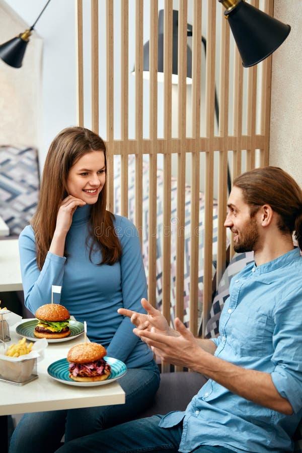 Coppie con gli hamburger in caffè immagine stock libera da diritti
