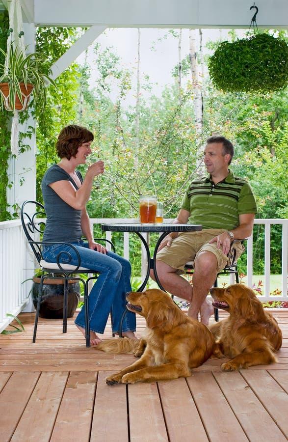 Coppie con i cani sul portico fotografia stock libera da diritti