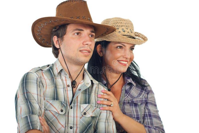 Coppie con i cappelli di cowboy che osservano al futuro immagini stock libere da diritti