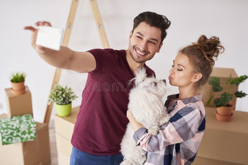 Coppie con il cane che fa un selfie nella nuova casa immagine stock