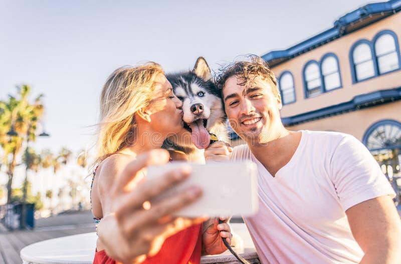 Coppie con il cane che prende selfie fotografia stock libera da diritti
