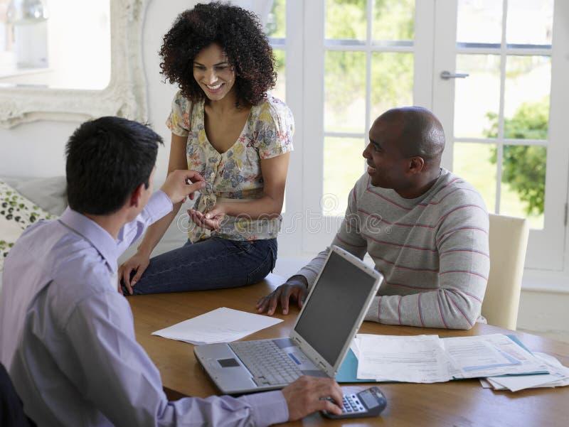Coppie con il consulente finanziario alla Tabella immagini stock libere da diritti