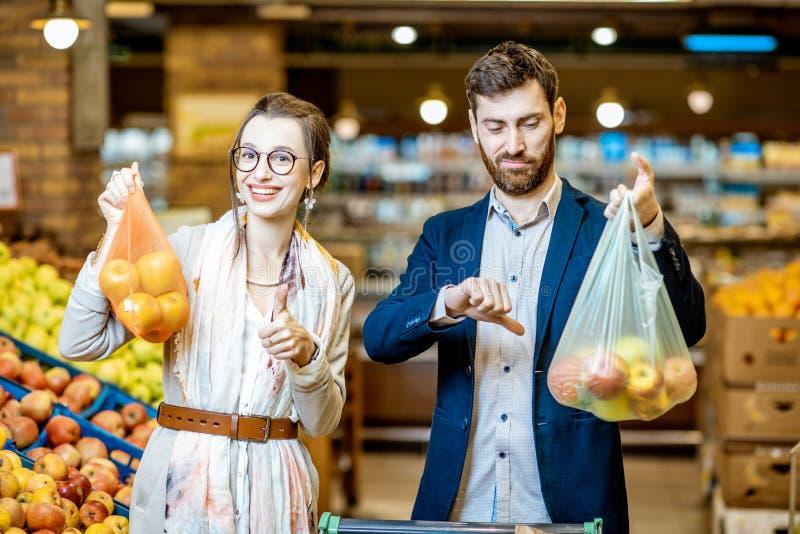 Coppie con il eco e sacchetto di plastica nel supermercato fotografia stock libera da diritti