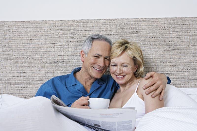 Coppie con il giornale della lettura della tazza di caffè a letto fotografia stock libera da diritti