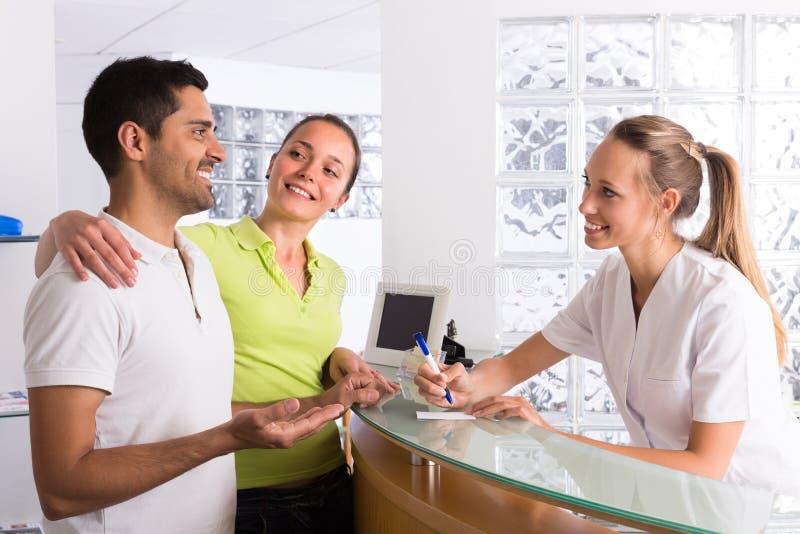 Coppie con il receptionist alla clinica fotografie stock libere da diritti