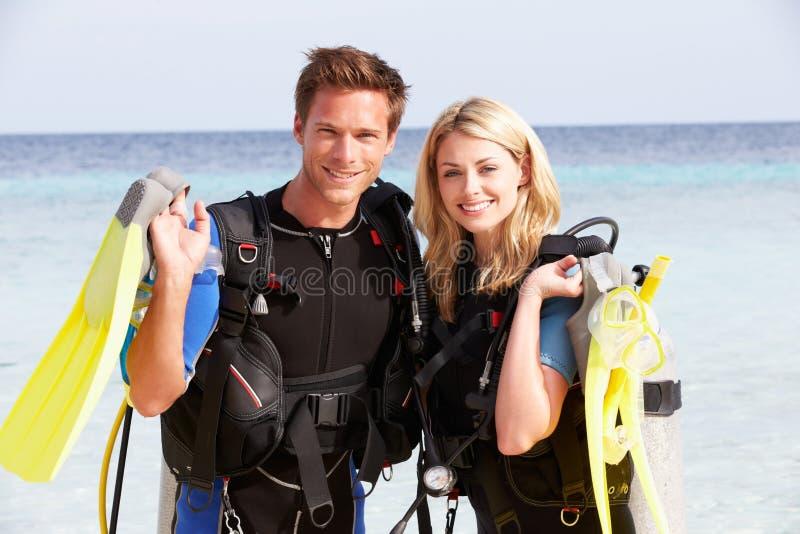 Coppie con l'attrezzatura di immersione con bombole che gode della festa della spiaggia immagini stock libere da diritti