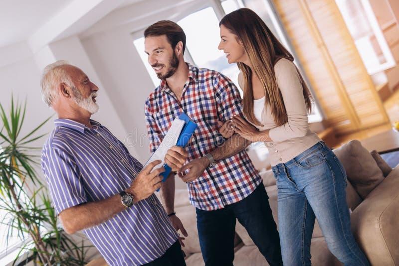 Coppie con la casa di visita dell'agente immobiliare da vendere immagini stock