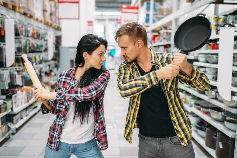 Coppie con la pentola ed il matterello in supermercato fotografia stock libera da diritti