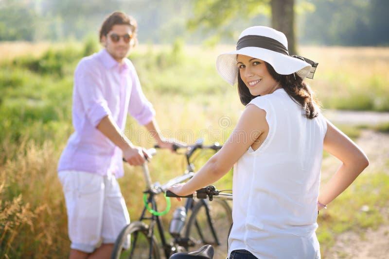 Coppie con le biciclette che sorridono verso la macchina fotografica immagine stock
