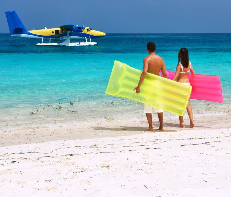 Coppie con le zattere gonfiabili che esaminano idrovolante sulla spiaggia fotografia stock libera da diritti