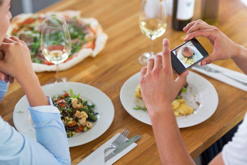 Coppie con lo smartphone che fotografa alimento al caffè immagine stock libera da diritti