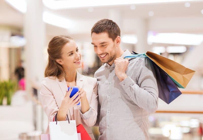 Coppie con lo smartphone ed i sacchetti della spesa in centro commerciale fotografie stock
