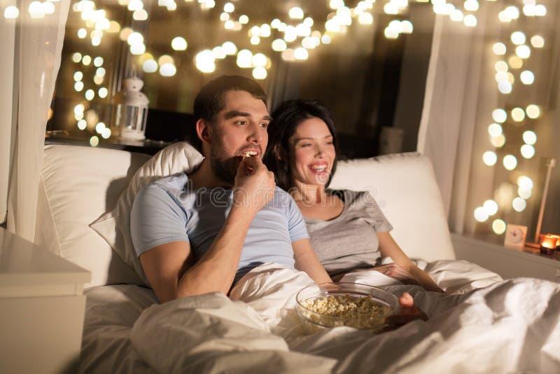 Coppie con popcorn che guarda TV alla notte a casa immagini stock
