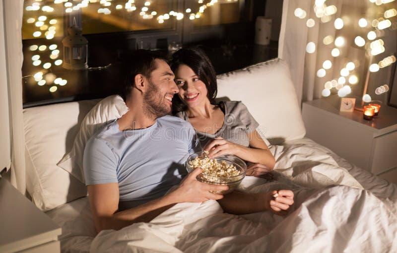 Coppie con popcorn che guarda TV alla notte a casa fotografia stock
