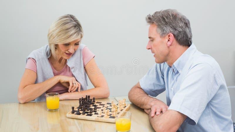 Coppie concentrate che giocano scacchi fotografia stock
