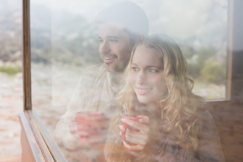 Coppie contente premurose con le tazze che guardano attraverso la finestra immagine stock
