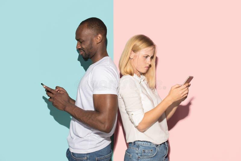 Coppie corse miste degli studenti che prendono i telefoni cellulari Ragazza caucasica e suo il ragazzo africano che posano allo s fotografia stock