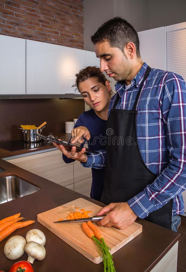 Coppie in cucina domestica che guarda ricetta con una compressa elettronica fotografia stock libera da diritti