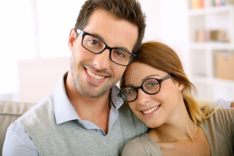 Coppie d'avanguardia con gli occhiali che si rilassano in sofà fotografia stock libera da diritti