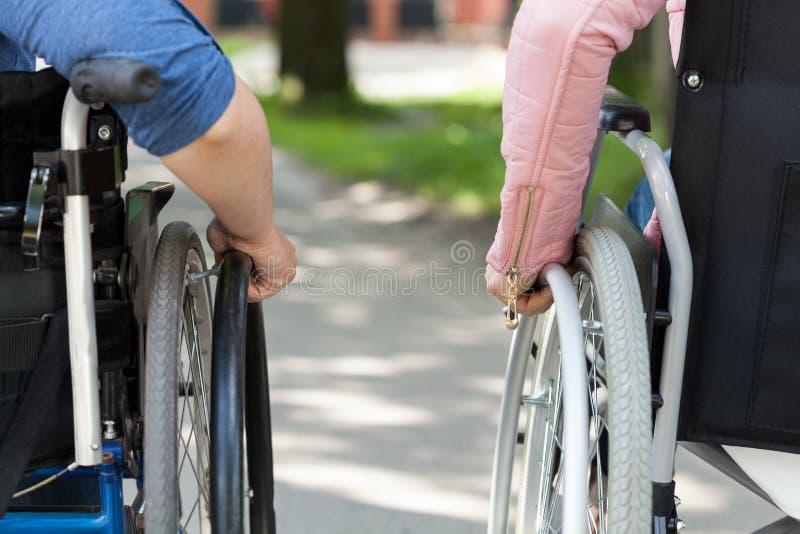 Coppie degli amici su una sedia a rotelle fotografie stock libere da diritti