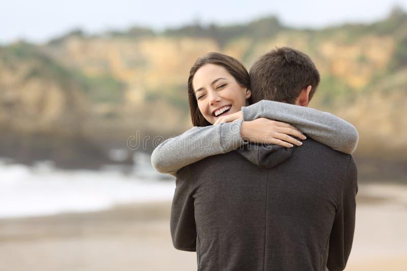 Coppie degli anni dell'adolescenza che abbracciano sulla spiaggia immagine stock