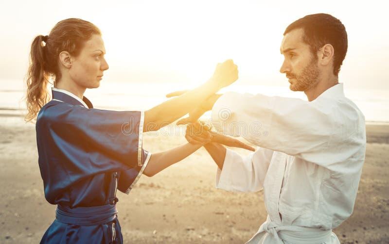 Coppie degli artisti marziali che si preparano sulla spiaggia immagine stock