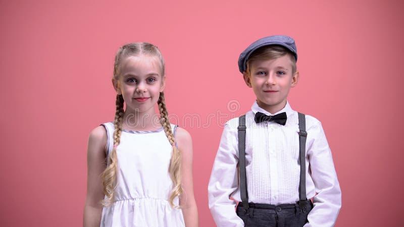 Coppie dei bambini che sorridono, esaminare macchina fotografica e celebranti giorno di biglietti di S. Valentino fotografia stock libera da diritti
