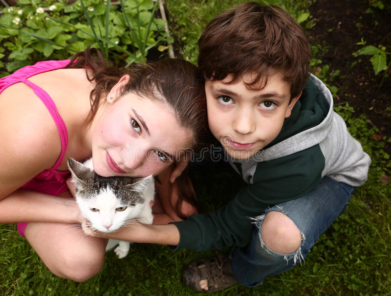 Coppie dei fratelli germani della sorella e del fratello con il gatto immagine stock libera da diritti
