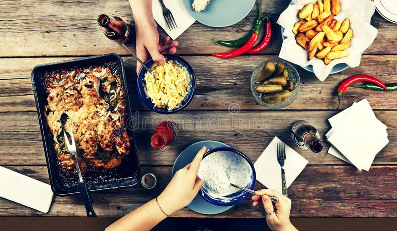 Coppie dei giovani alla tavola di cena con vari alimenti, coscie di pollo al forno, barbecue delle patate, birra, sottaceti e spu fotografia stock