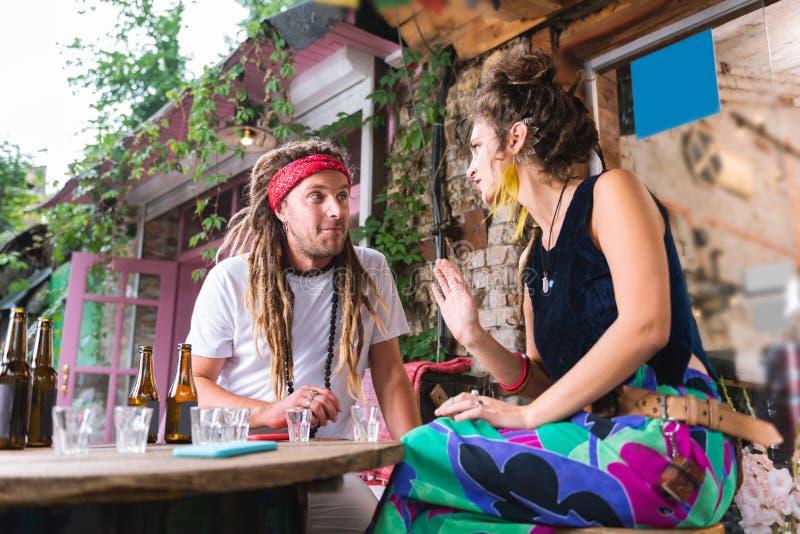 Coppie dei hippy che ritengono emozionali mentre discutendo qualcosa immagine stock