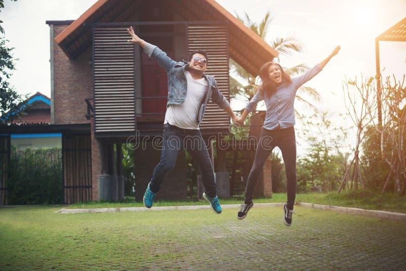 Coppie dei pantaloni a vita bassa che saltano su nella campagna Coppie nell'amore c fotografia stock