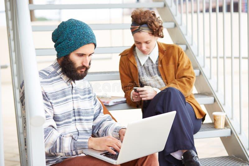 Coppie dei pantaloni a vita bassa facendo uso del computer e dello smartphone all'aperto immagine stock
