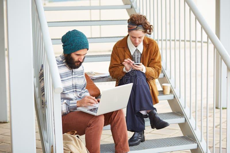 Coppie dei pantaloni a vita bassa facendo uso del computer e dello smartphone all'aperto immagini stock libere da diritti