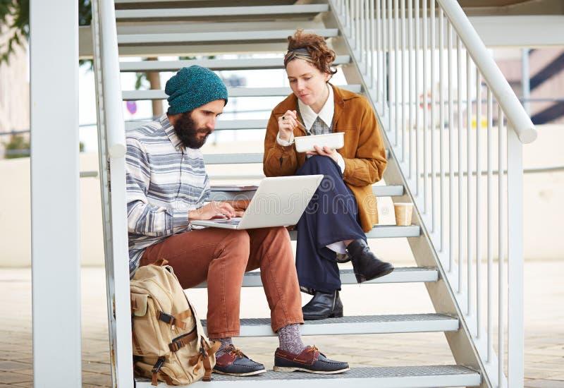 Coppie dei pantaloni a vita bassa facendo uso del computer e di cibo del pranzo all'aperto fotografia stock libera da diritti