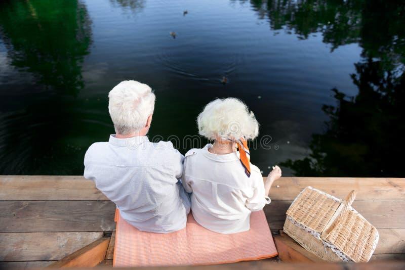 Coppie dei pensionati che si siedono vicino alle loro anatre d'alimentazione del paniere in lago immagini stock