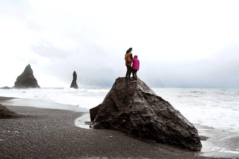 Coppie dei turisti che stanno su una roccia su una spiaggia nera in Icelan immagini stock