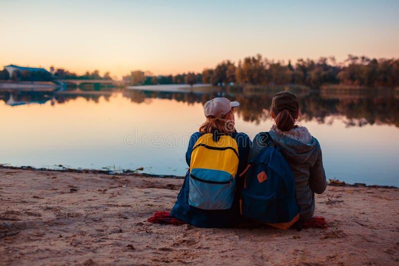 Coppie dei turisti con gli zainhi che si rilassano dalla sponda del fiume di autunno Acqua potabile delle donne allegre e resto a fotografie stock libere da diritti