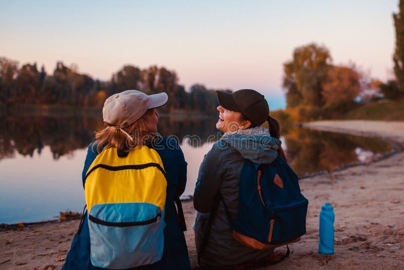 Coppie dei turisti con gli zainhi che si rilassano dalla sponda del fiume di autunno Acqua potabile delle donne allegre e resto a immagini stock libere da diritti