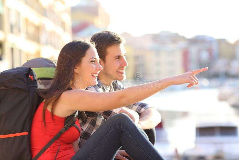 Coppie dei viaggiatori con zaino e sacco a pelo che indicano punto di riferimento nella via fotografia stock