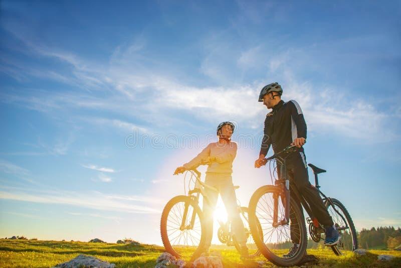 Coppie del ciclista con i mountain bike che stanno sulla collina sotto il cielo di sera e che godono del sole luminoso al tramont fotografia stock libera da diritti