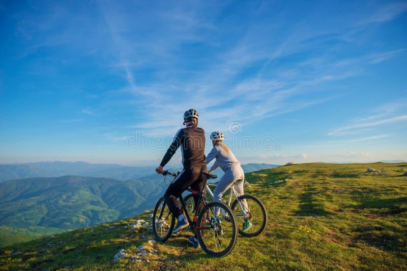 Coppie del ciclista con i mountain bike che stanno sulla collina sotto il cielo di sera e che godono del sole luminoso al tramont immagini stock