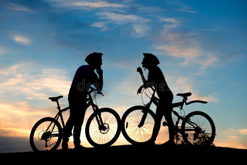 Coppie del ciclista sulla collina al tramonto immagine stock