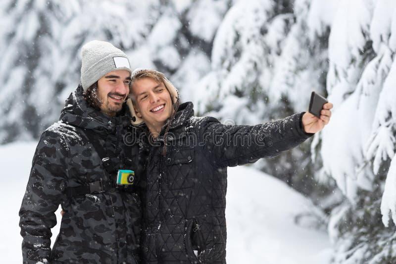 Coppie del giovane che prendono la foto di Selfie in neve Forest Outdoor Guys Holding Hands fotografia stock