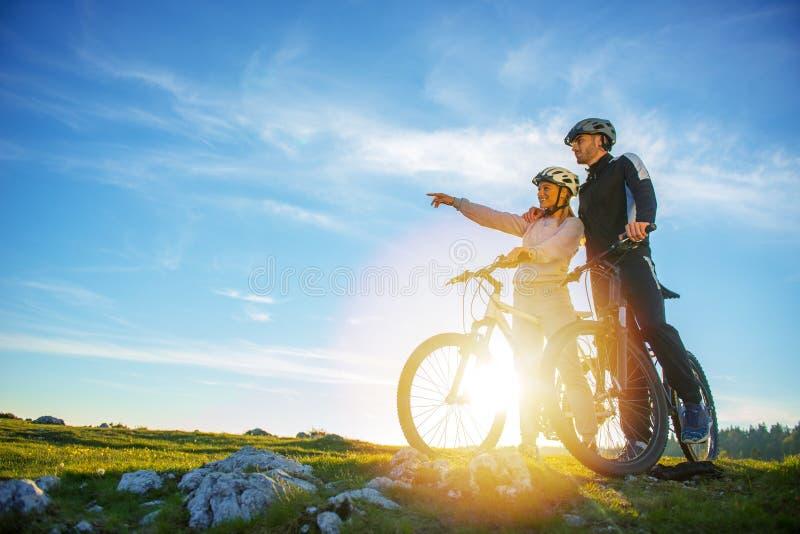 Coppie del motociclista con il mountain bike che indica nella distanza alla campagna fotografia stock