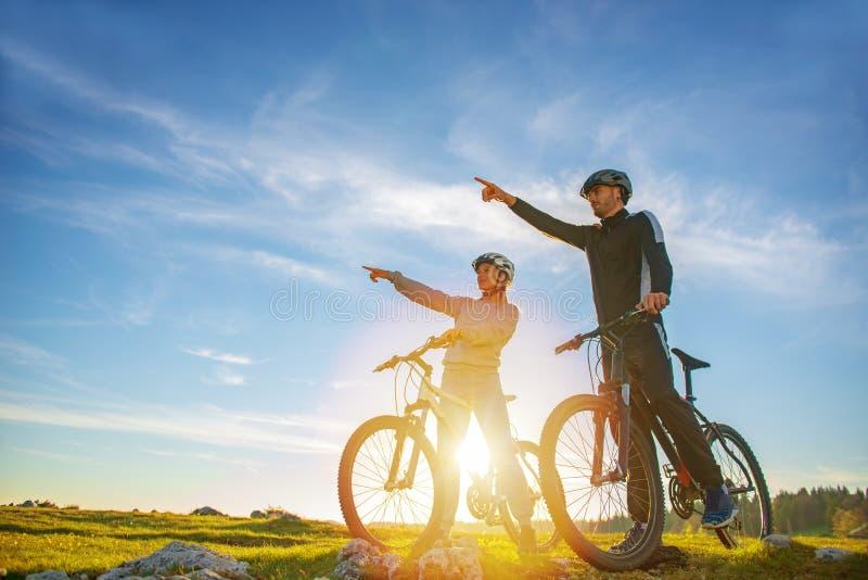 Coppie del motociclista con il mountain bike che indica nella distanza alla campagna fotografie stock