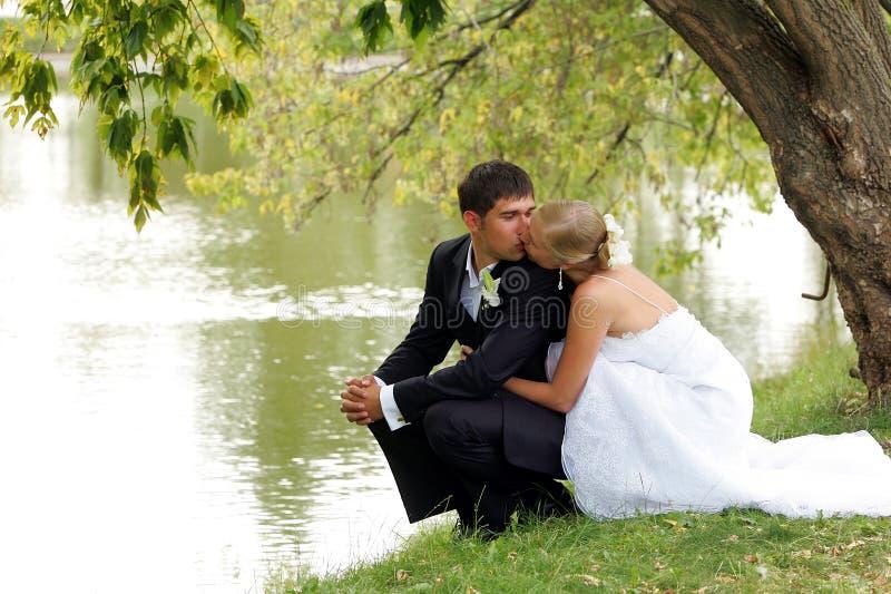 Coppie del Newlywed che baciano dal lago fotografia stock