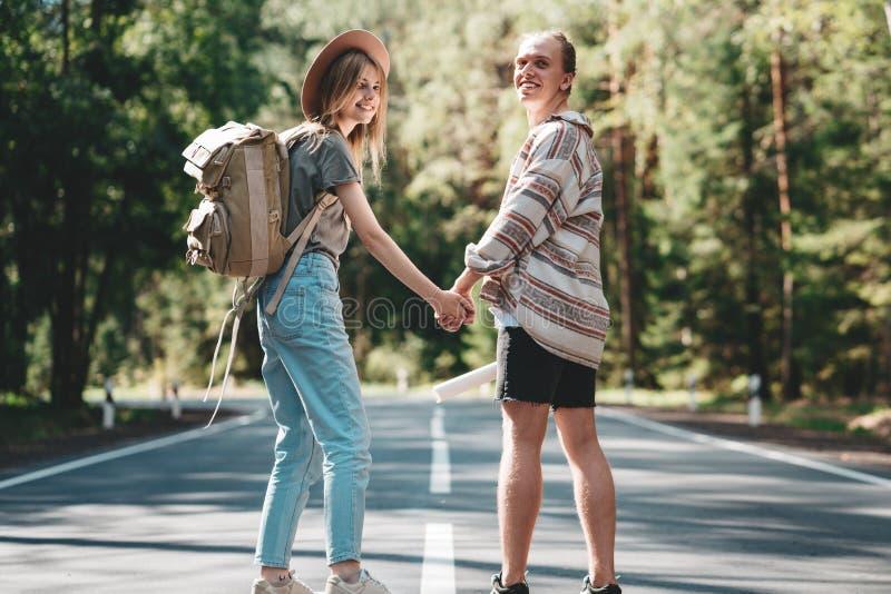 Coppie del viaggiatore nell'amore che gode tenendosi per mano e guardando in avanti ad un viaggio unito immagine stock libera da diritti