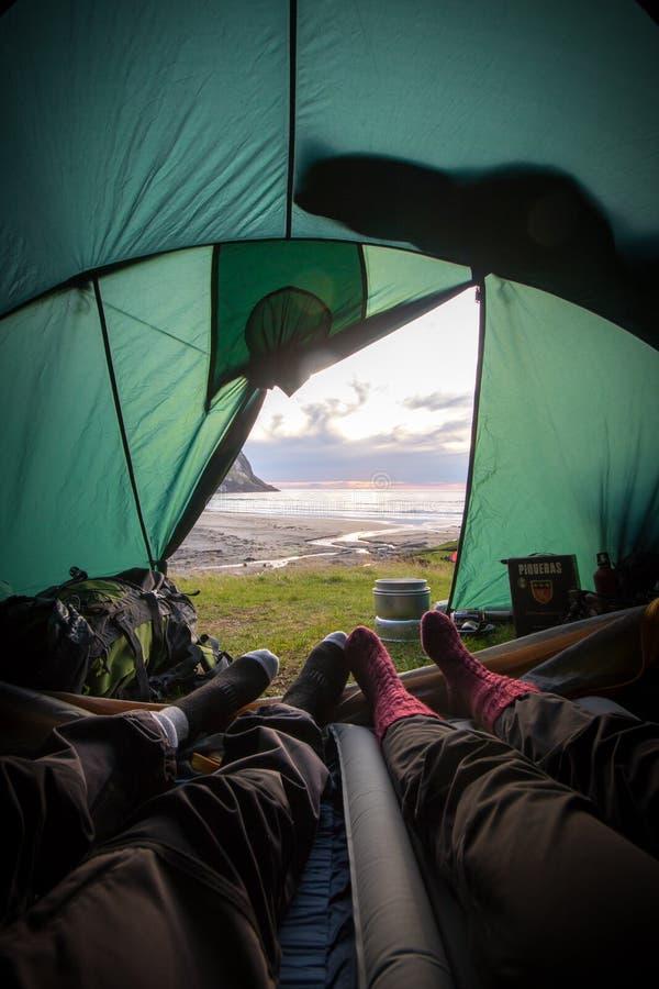 Coppie del viaggiatore in una tenda che esamina un bello tramonto immagini stock