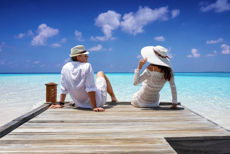 Coppie del viaggiatore in vestiti bianchi che si siedono su un molo di legno immagine stock libera da diritti
