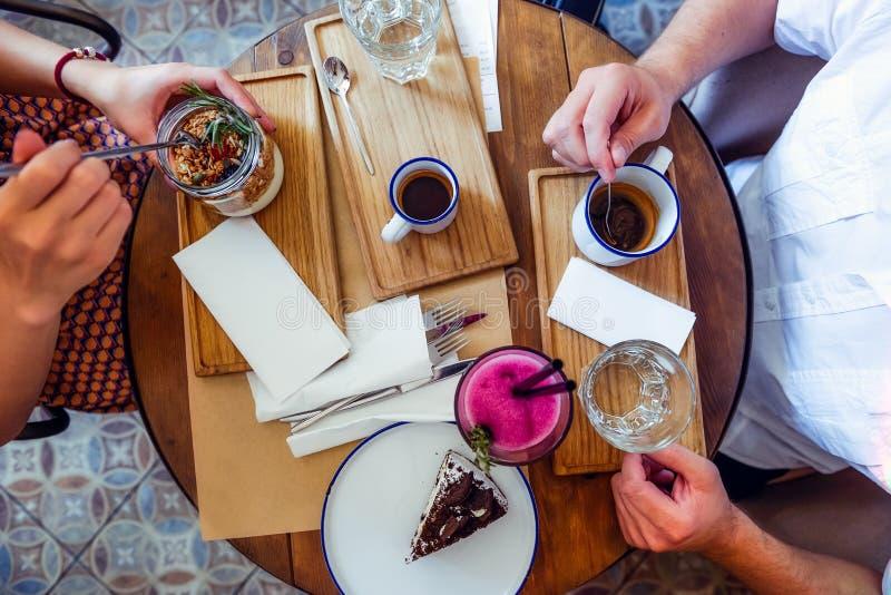 Coppie dell'uomo e della donna alla data che mangia prima colazione di mattina in caffè Granola, dolce di cioccolato, frullato e  fotografia stock